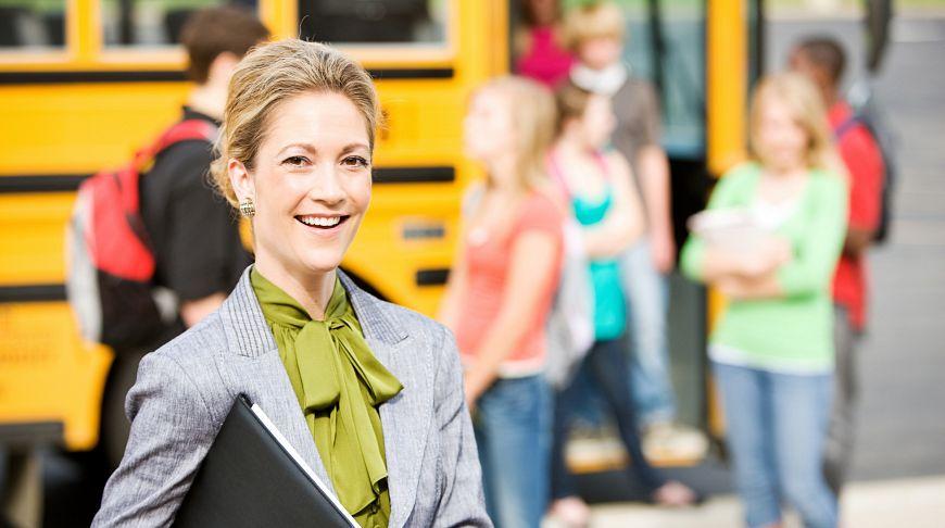 учитель возле школьного автобуса